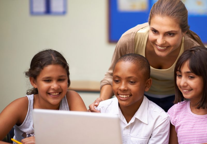 Educational Technology Online Graduate Certificate Image of Teacher Working with Children in Front of a Computer