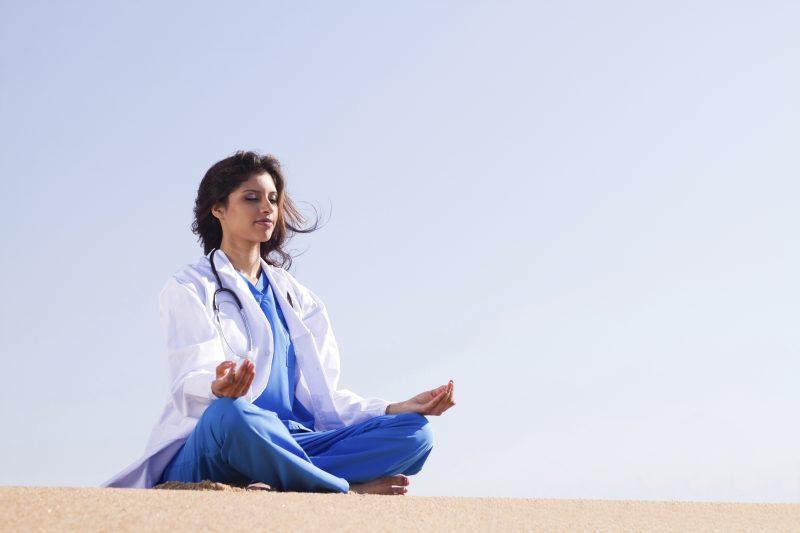 Holistic Nursing Online Graduate Certificate Image of Holisting Nurse Performing Yoga on Beach