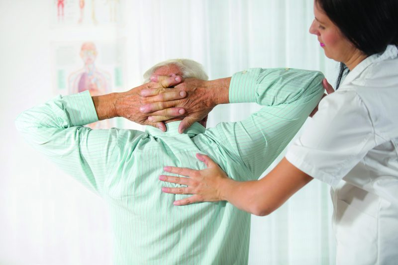 Pain Management Online Graduate Certificate Image of Nurse Pain Specialist Helping Patient Using Applied Back Pressure